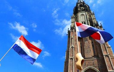 Nederlandse vlaggen en klompen op de foto met de Nieuwe Kerk op de achtergrond